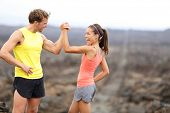 stock photo of cheers  - Fitness sport running couple celebrating cheerful and happy giving high five energetic and cheering - JPG