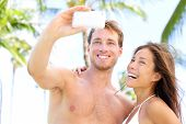Vacation couple on beach taking pictures with camera phone. Romantic couple photographing self-portr