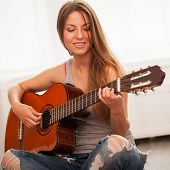 Young beautiful caucasian woman in casual playing guitar