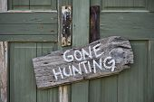 stock photo of shotguns  - Gone hunting sign on old antique door - JPG