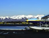 picture of float-plane  - Snow covered mountains and a blue float plane - JPG