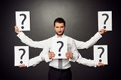 foto of interrogation  - serious businessman with five hands holding placards with question marks - JPG