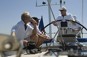 image of watersports  - Sailors talking at the helm on a yacht against clear blue sky - JPG