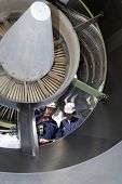 two airplane mechanics standing inside large jumbo jet engine