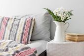pic of pillowcase  - White flowers and books on a side table near a bed - JPG
