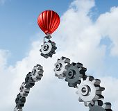 stock photo of gear wheels  - Business bridge building with a red hot air balloon lifting a gear up to the sky to construct and complete a bridged chain of cogs connected together as a result of strategy and planning for success - JPG