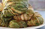 image of kimchi  - Wrapped and uncut Korean Kimchi on a plate waiting to be cut up - JPG