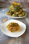 image of kimchi  - A plate of sliced and stacked kimchi and a plate of wrapped and uncut kimchi - JPG