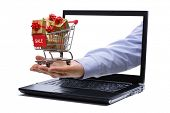 Shopping cart full of gold gift boxes and red sale sign through laptop monitor concept for e-commerc