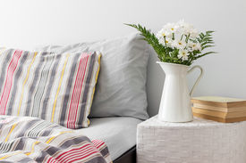 stock photo of pillowcase  - White flowers and books on a side table near a bed - JPG