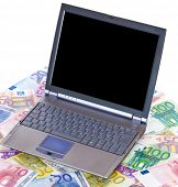 Standard laptop on various euro notes. All on white background.
