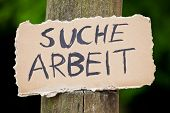 Cardboard sign showing the german term Suche Arbeit. English translation: looking for a job