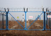 industry danger - locked gate with barbed wire