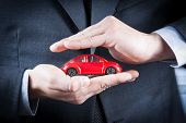 Businessman Protect With His Hands A Red Car, Concept For Insurance, Buying, Renting, Fuel Or Servic