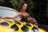 woman in leopard dress posing with hot rod