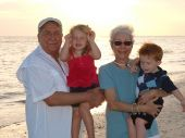 Grand parents on the beach with grandchrildren