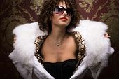 foto of frizzle  - Portrait of beautiful curly young girl in furs and sunglasses - JPG