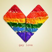 an origami heart painted as the rainbow flag and the sentence gay love on a beige background, with a retro effect