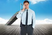 Serious businessman holding his jacket against book steps leading to door against sky