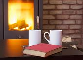 Home interior with fireplace, red book and tea on table