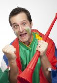 stock photo of groupies  - Excited sports fan with red plastic vuvuzela horn - JPG