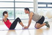 Full length side view of a male trainer helping young woman do abdominal crunches in the bright gym