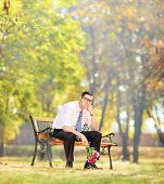 Sad young man holding a bouquet of flowers and sitting on a bench in a park, shot with a tilt and shift lens