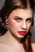 Portrait of young beautiful woman with stylish red eyeliner and glossy lipstick