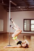 image of pole dance  - young pretty girl pole dancing in a dance hall - JPG