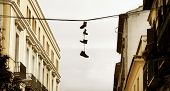 Urban Landscape With Boots Hanged On A Wire