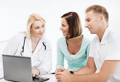 healthcare, medical and technology - doctor with patients looking at laptop