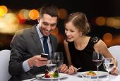 restaurant, technology, couple and holiday concept - smiling couple taking picture of main course wi
