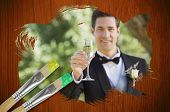 Composite image of groom toasting with champagne with paintbrush dipped in green against wooden oak