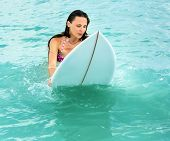 Attractive Young Girl On Surfboard In Ocean