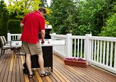 Mature Man Turning On Barbecu Grill While Outside On Open Deck