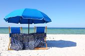 Two Beach Chairs Under A Blue Umbrella On A White Sandy Beach