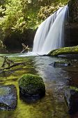 Waterfall with green reflection in water with mossy rocks