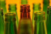 Ten Empty Beer Bottles Shot With Orange Light. Nine Green Bottles And One Brown.