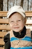 Little Boy In A Cap Outdoors