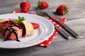 Tasty homemade strudel with ice-cream, fresh strawberry and mint leaves on plate, on wooden backgrou