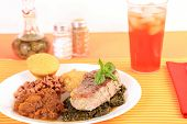 picture of sweet pea  - Thick juicy pork chop on bed of collard greens with black eyed peas and creamed corn and sweet candied yams with pineapple and pecans - JPG