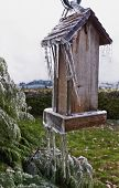 Old Wooden Bird feeder with icicles hanging from post