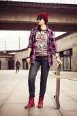 Brunette woman in hipster outfit scateboarding on the street. Toned image