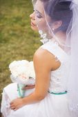 Beautiful Bride Preparing To Get Married In White Dress And Veil With Bouquet Of Roses In The Park A