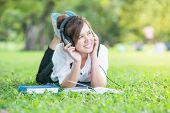Asian Student With Headphones Outdoors. Enjoying Music