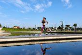 woman running over bridge with fitness marathon training stride