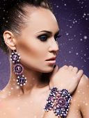 Close-up portrait of young and beautiful lady in a precious earrings and a bracelet on her hand. Winter background with a snow.