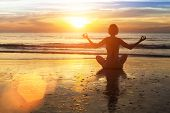 Silhouette of a woman practicing yoga on the beach in the glow of an amazing sunset.