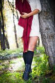 woman wearing white wool dress, red wool  scarf and leather boots, outdoor shot in autumn park