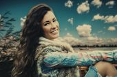 beautiful young woman with dazzling smile in fur vest, wool scarf and blue tartan shirt, blue sky with fluffy clouds and river in background, pleasant winter day